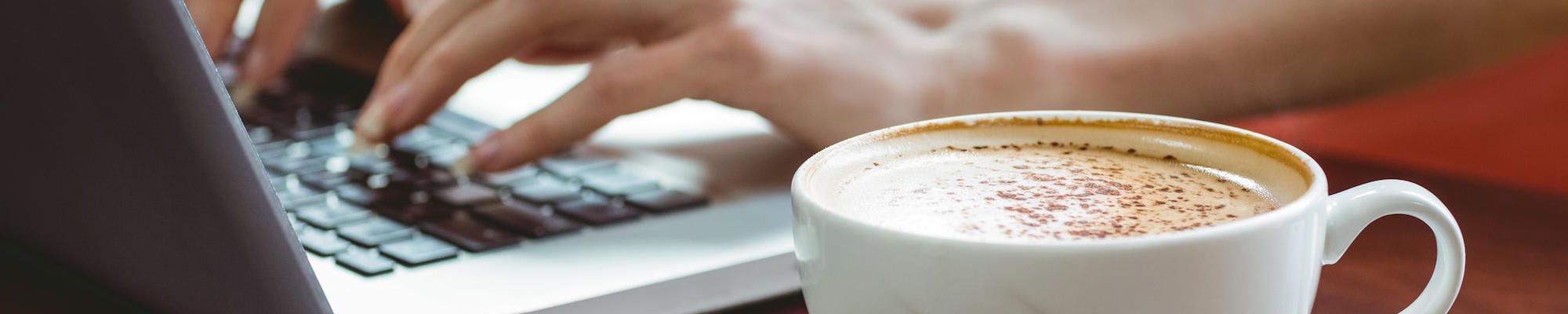 Hands on a laptop and a cup of coffee